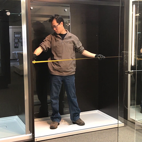 fleurco installer measuring the middle opening of shower enclosure