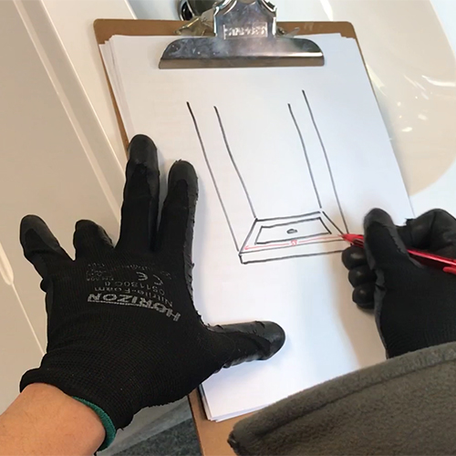 fleurco installer marking down the bottom measurement on their drawing